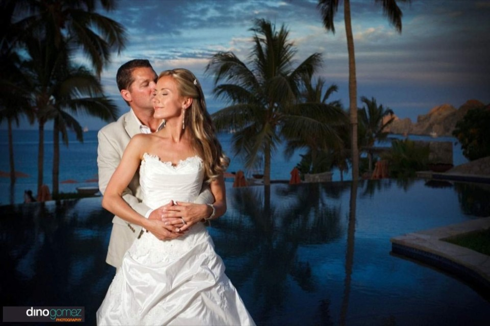 Simply Breathtaking Bride And Groom Loving Embrace With The Pool And Beach As The Back Drop