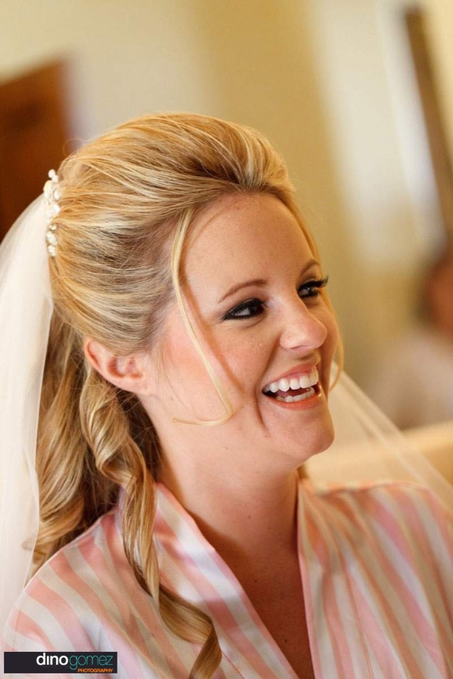 Beautiful bride to be smiling in her robe and veil before the wedding ceremony