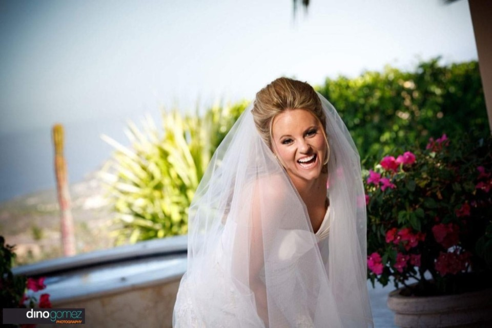 Beautiful bride laughing and bending next to some beautiful pink flowers