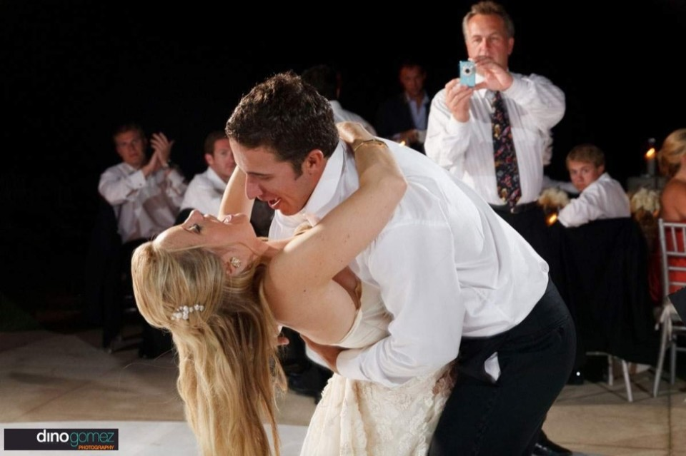Groom dipping the bride back on the dance floor in Mexico