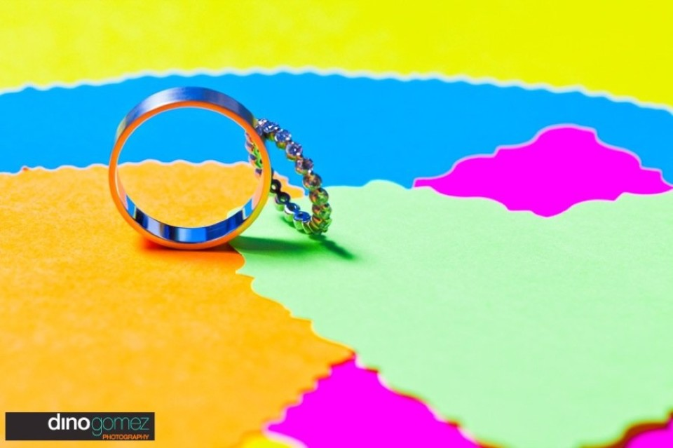 This is a photo of two wedding rings on top of some coloured paper