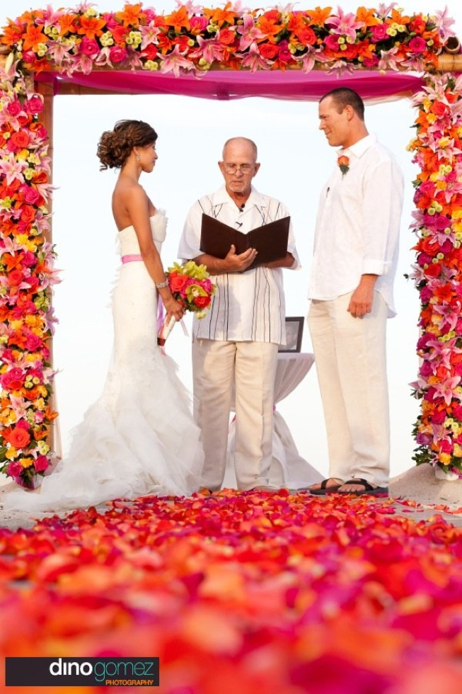 Bride and groom exchanging vows with wedding official under a colourful floral arch