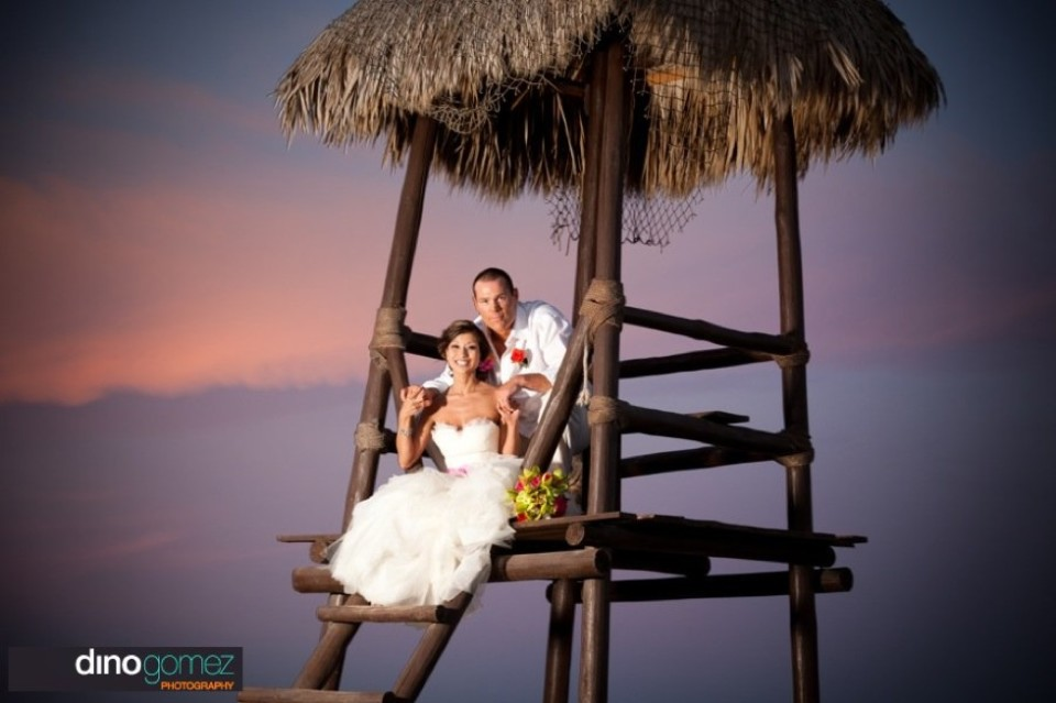 Bride and groom sitting outside in beach hut with thatch roof