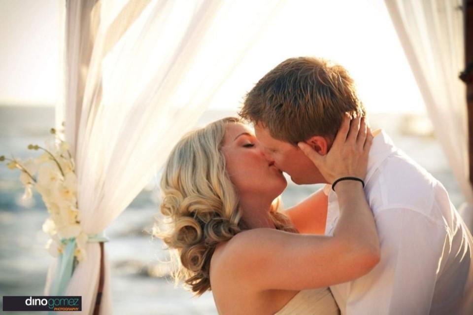 A blonde bride kisses her husband at their destination wedding, taken by Dino Gomez