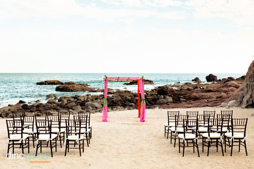 A stunning altar is set up on the beach in front of chairs, ready for a destination wedding.