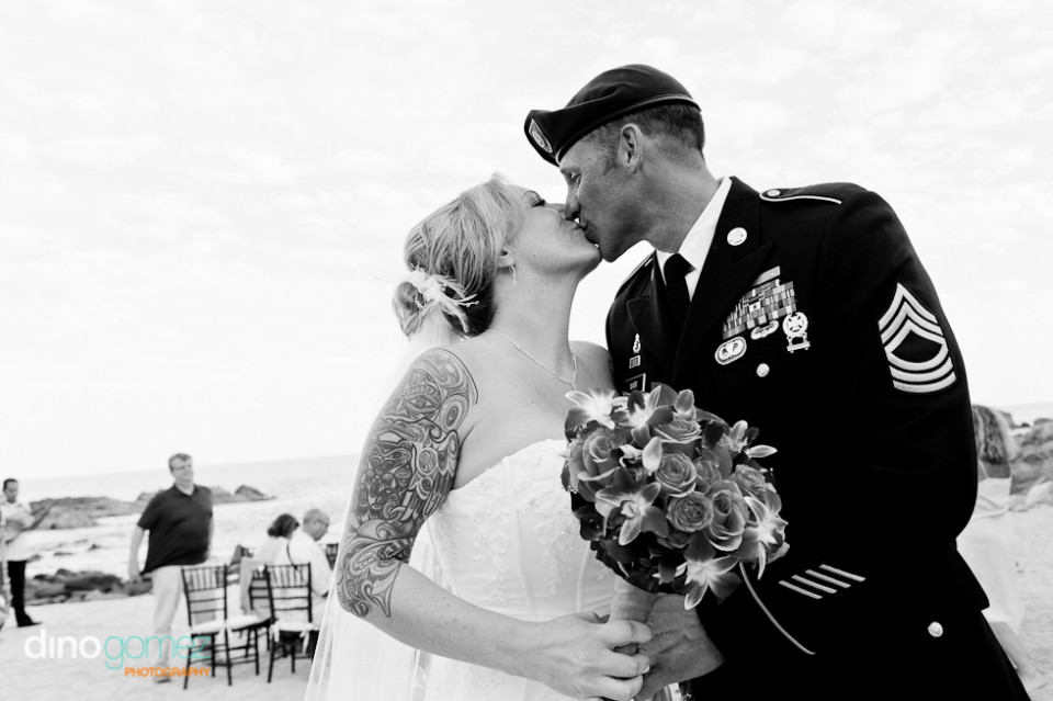 A beautiful bride with a tattoo kisses her husband who is in uniform