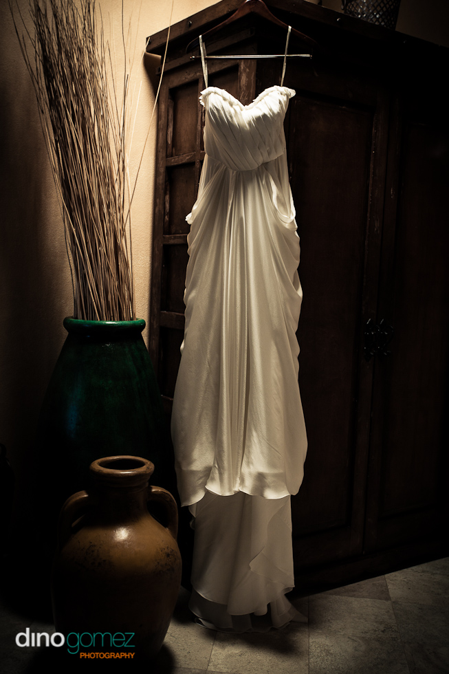 Bride's wedding dress hanging from a rustic wardrobe