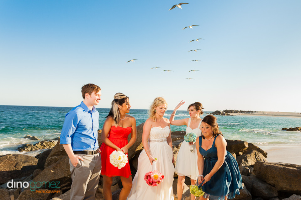 Destination wedding bride and bridesmaid and groom on the beach with seagulls flying above