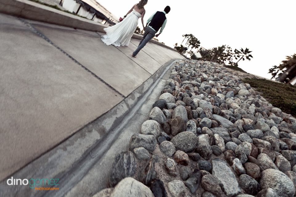 Bride and Groom walking away from destination wedding photographer Dino Gomez