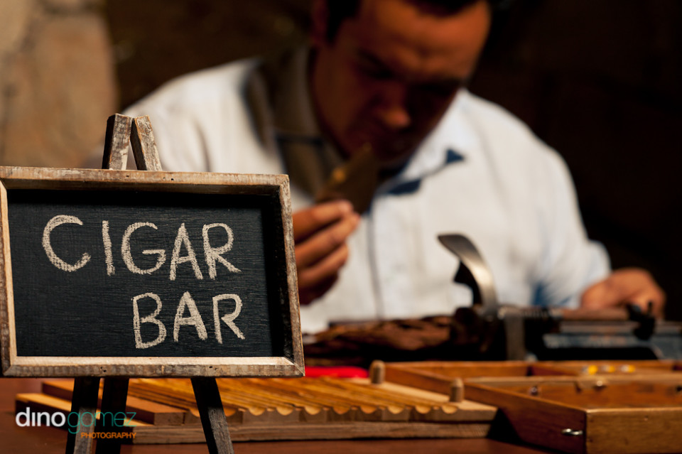 Wedding cigar bar sign with main in a blue shirt in the background