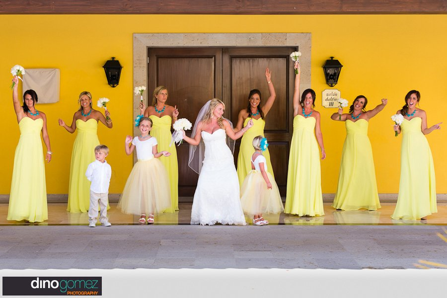 Wedding shot of bride and bridesmaid in yellow dresses and cute flower girls and ring bearer