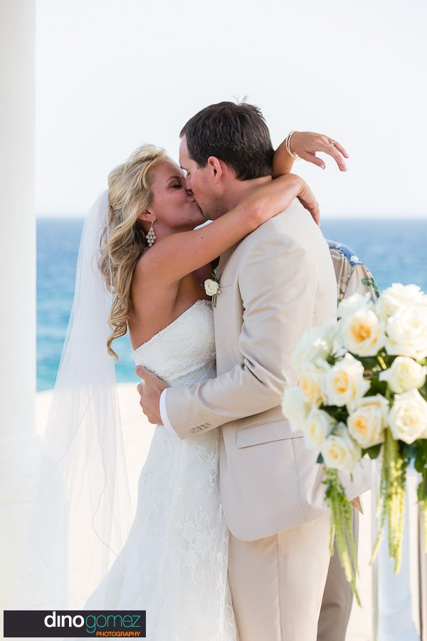 Gorgeous shot of the newlyweds kissing on wedding day