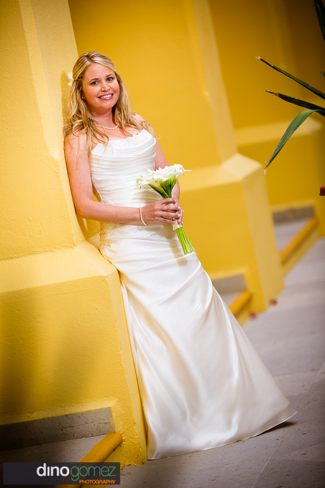 Very cool shot of the bride alone leaning on bright yellow columns