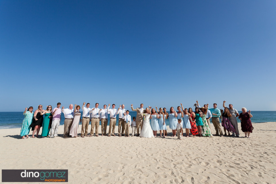 Wedding party and guests standing in a line on the beach