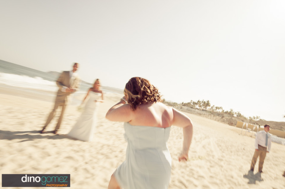 Bridesmaid having fun on the sand with the newlyweds in the background