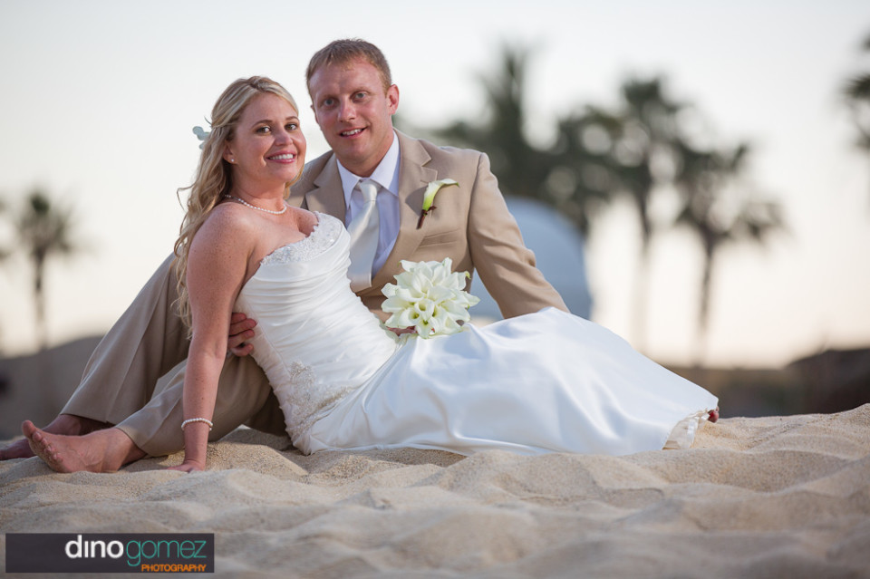 Cute couple sitting on the sand after getting married