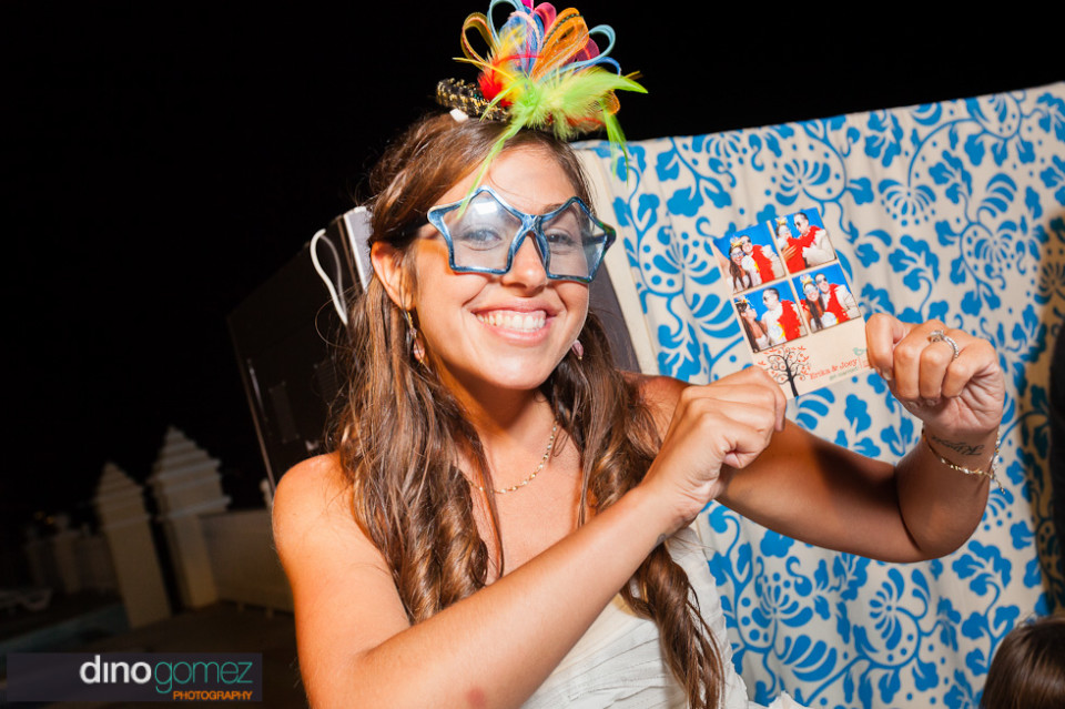 Gorgeous lady in a star shaped glasses holding up a shot from the photo booth