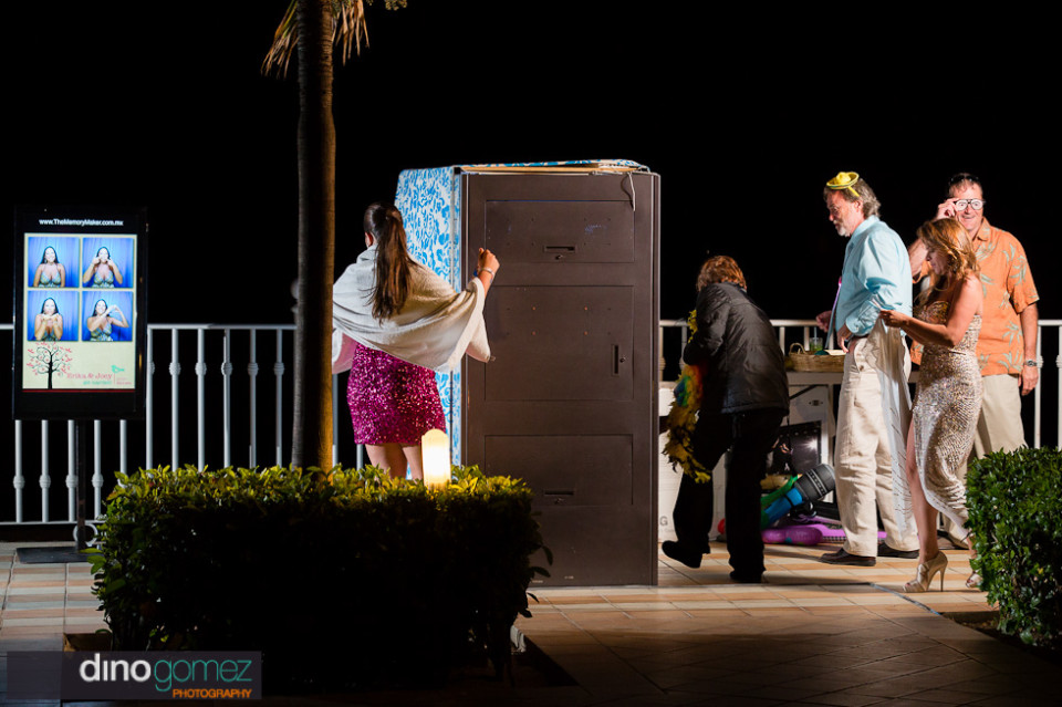 A snapshot of a few wedding guests next to the photo booth in Mexico