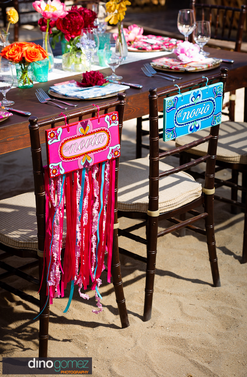 Fun looking bride and groom wedding chair with the signs in Spanish