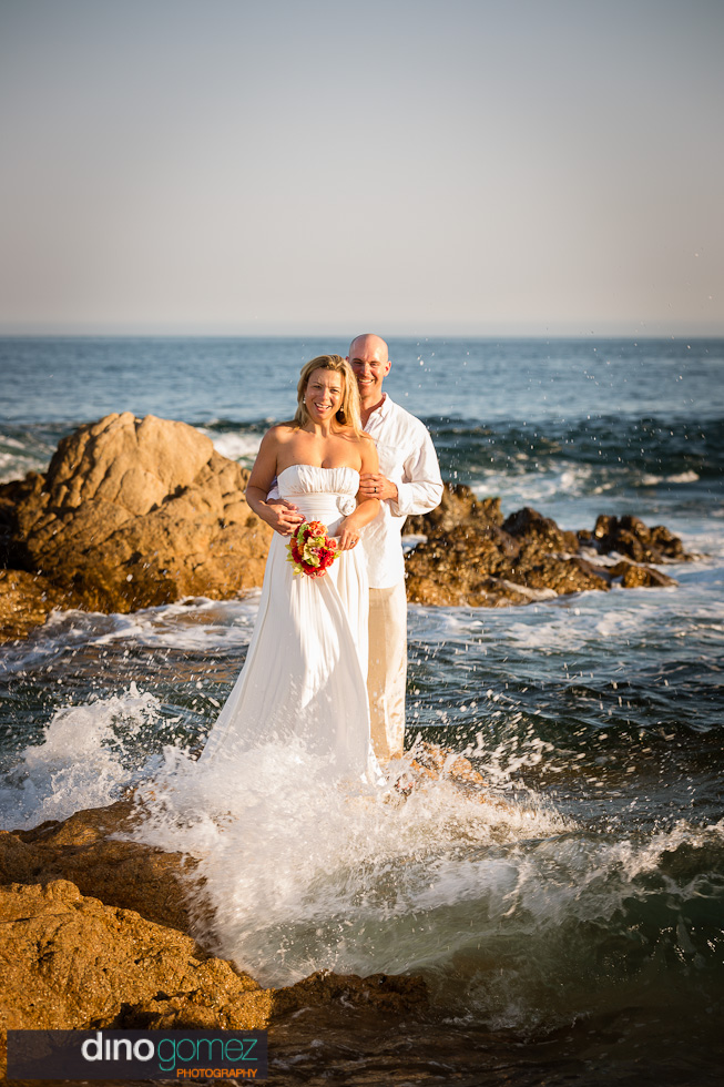 Bride and groom standing together on the rocky beach in Mexico