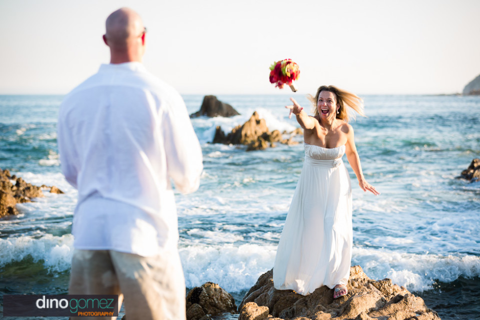 Bride tossing bouquet to the groom on the beach