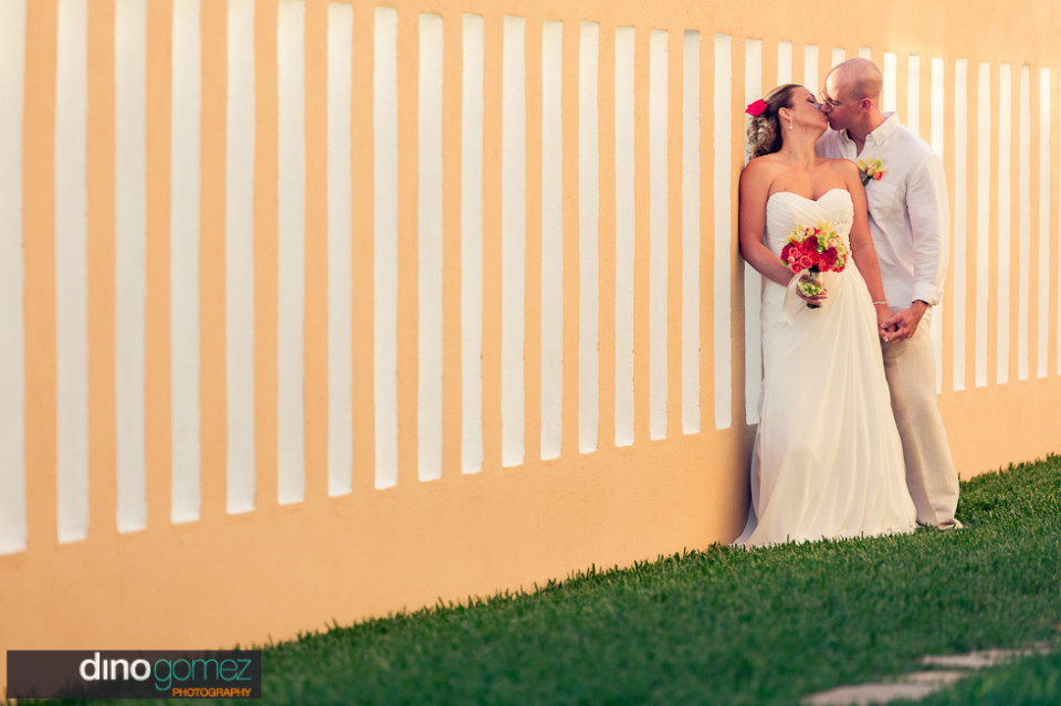 Wedding couple kissing in front of a peach wall with white stripes