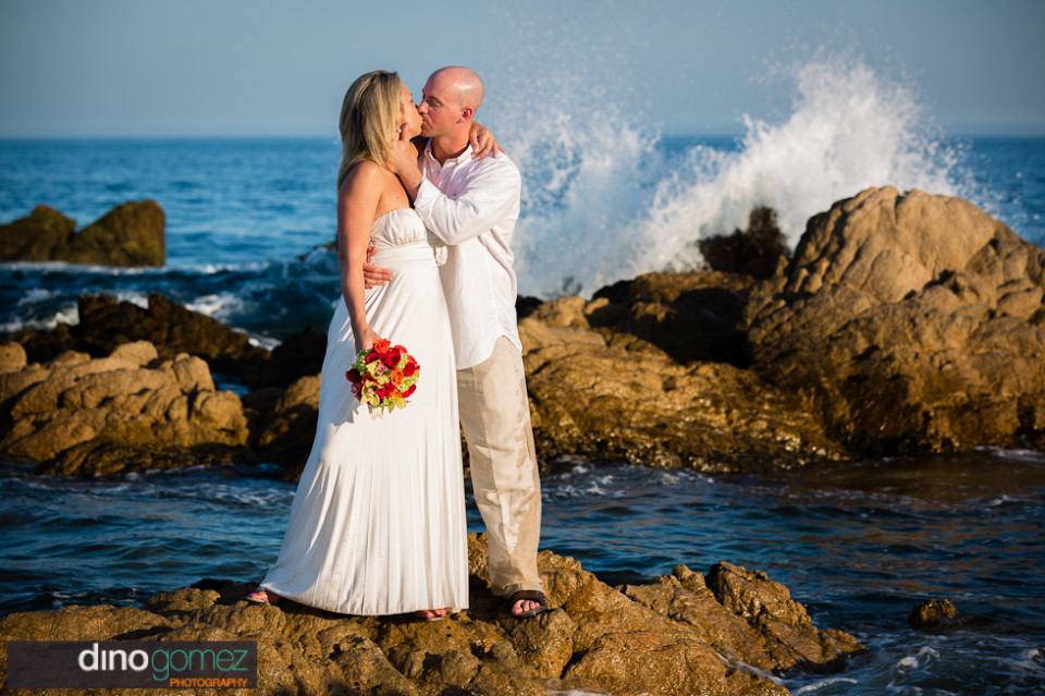 Wedding couple sweet kiss on the beach after the ceremony