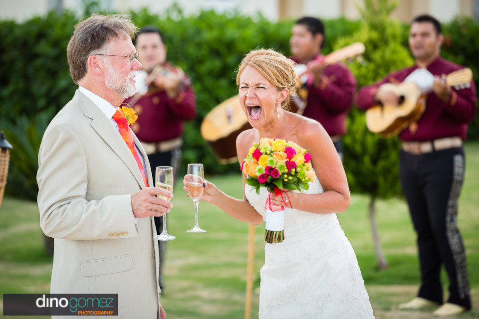 An excited bride and groom drinking champagne on their wedding day