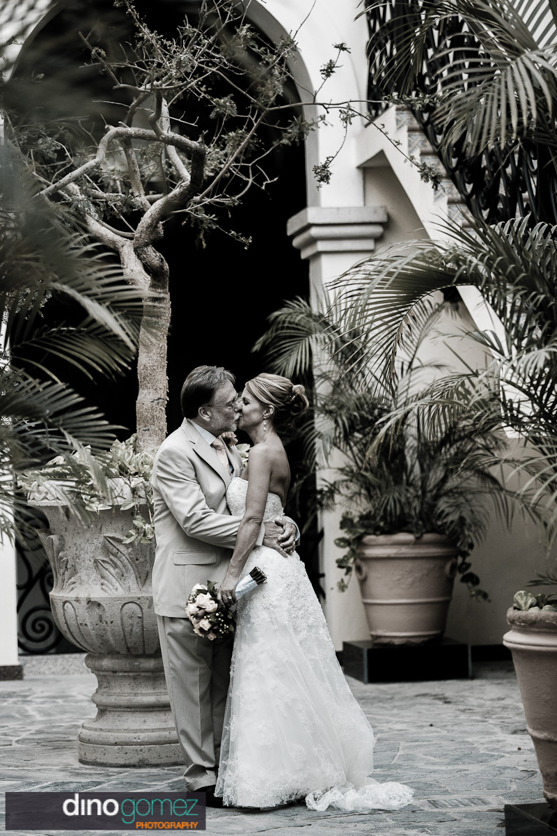 Beautiful black and white shot of the bride and groom kissing at their destination wedding