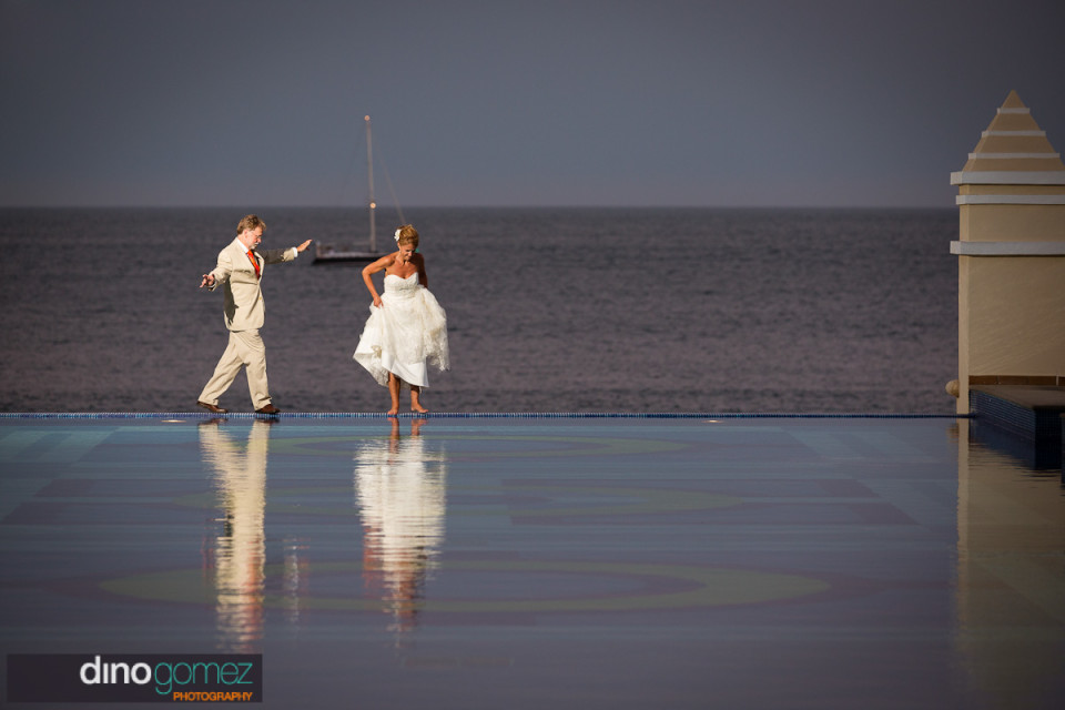 Bride and groom standing on the edge of pool with the beautiful ocean in the background
