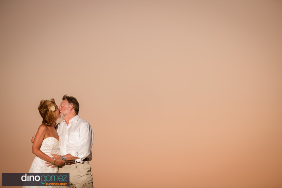 Bride and groom kissing at sunset at their destination wedding